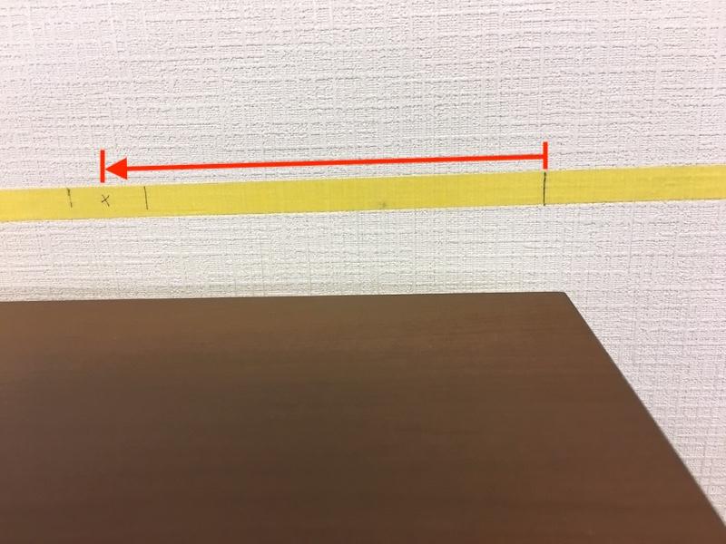 家具を設置場所に置き、紙テープ上で家具の両サイドの線を引きます。 家具の左右側面から何cmにマーキングがあるか測ります。