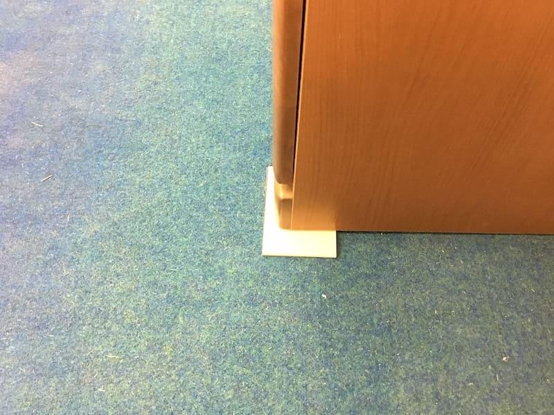 そこで、家具の前面下に板などを差し込み家具を壁に密着させます。